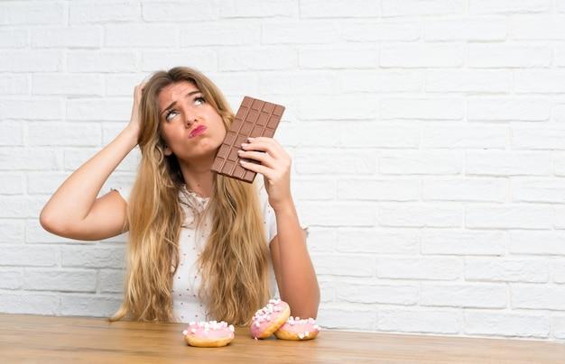 Junge blonde frau mit der schokolade, die zweifel hat