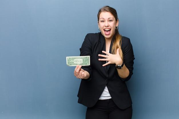 Junge blonde frau mit dollarbanknoten gegen schmutzwandhintergrund