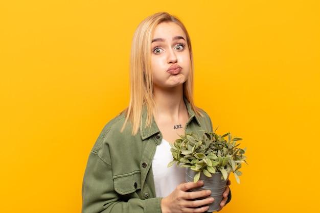 Junge blonde frau mit einem albernen, verrückten, überraschten ausdruck, puffwangen, sich gestopft, fett und voller essen fühlen