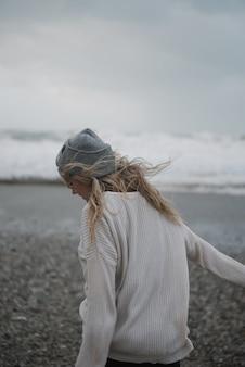 Junge blonde frau mit einem hut, der auf einer felsigen seeküste in einem windigen wetter geht