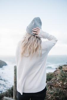 Junge blonde frau mit einem hut, der spaß am strand bei windigem wetter hat
