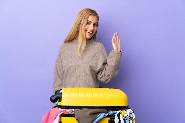 Junge blonde frau mit einem koffer voller kleidung über isolierter lila wand, die mit hand mit glücklichem ausdruck salutiert