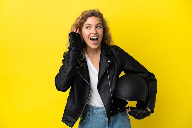 Junge blonde frau mit einem motorradhelm isoliert auf gelbem hintergrund, der etwas hört, indem sie die hand auf das ohr legt