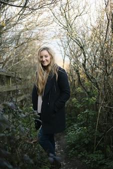 Junge blonde frau mit einem schwarzen mantel, der auf einem weg steht, der von blattlosen bäumen umgeben ist