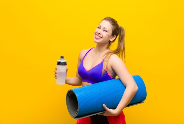 Junge blonde frau mit einem yogamatten-sportkonzept