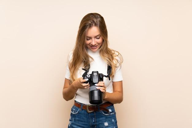 Junge blonde frau mit einer berufskamera