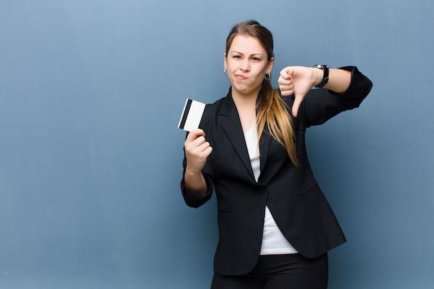 Junge blonde frau mit einer kreditkarte gegen schmutzwand