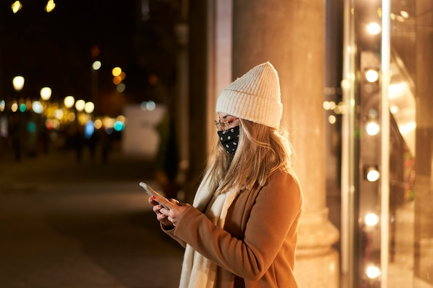 Junge blonde frau mit einer maske vor einem schaufenster, das eine nachricht in einer stadt in der nacht mit lichtern im hintergrund schreibt. winteratmosphäre.