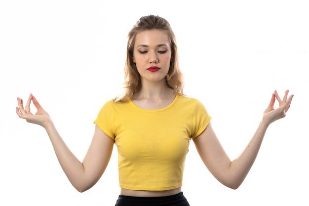 Junge blonde frau mit gelbem t-shirt meditieren