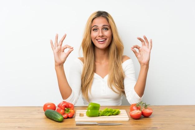 Junge blonde frau mit gemüse in einer tabelle, die ein okayzeichen mit den fingern zeigt