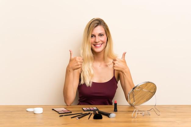 Junge blonde frau mit kosmetik in einer tabelle, die daumen gibt, up geste