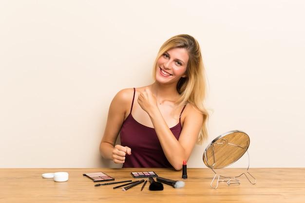 Junge blonde frau mit kosmetik in einer tabelle, die einen sieg feiert