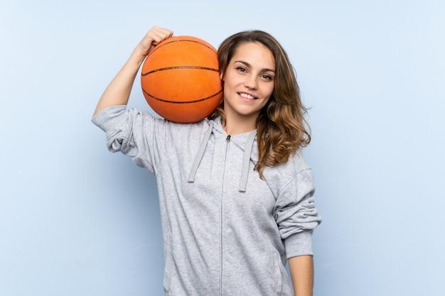 Junge blonde frau mit kugel des basketballs