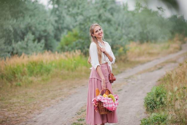 Junge blonde frau mit langen haaren im retro-stil vintage-kleidung mit picknickkorb zu fuß auf landung