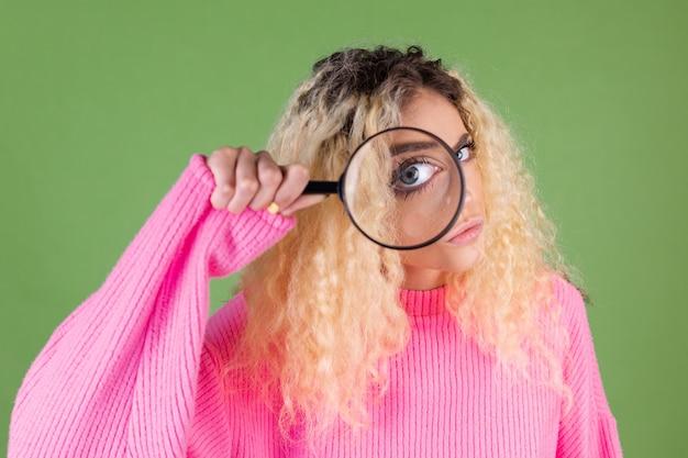 Junge blonde frau mit langen lockigen haaren in rosa pullover auf grün mit lupe