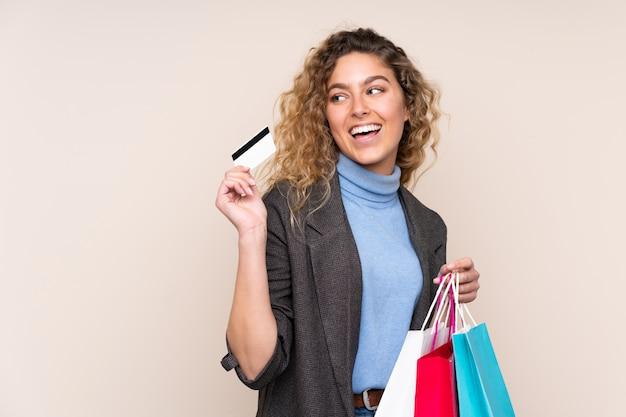 Junge blonde frau mit lockigem haar auf beige wand, die einkaufstaschen und eine kreditkarte hält