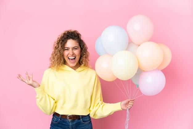 Junge blonde frau mit lockigem haar, das viele luftballons fängt, die auf rosa unglücklich und mit etwas frustriert lokalisiert werden