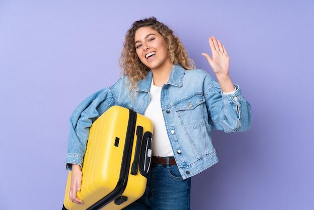 Junge blonde frau mit lockigem haar lokalisiert auf purpur im urlaub mit reisekoffer und gruß