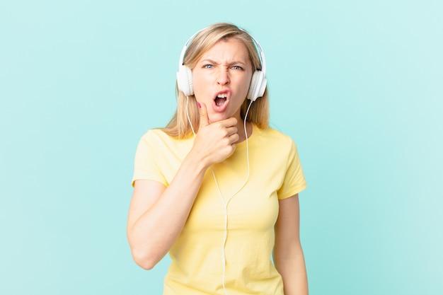 Junge blonde frau mit mund und augen weit offen und hand am kinn und musik hören.