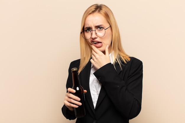 Junge blonde frau mit offenem mund und weit geöffneten augen und hand am kinn, die sich unangenehm geschockt fühlt und sagt, was oder wow