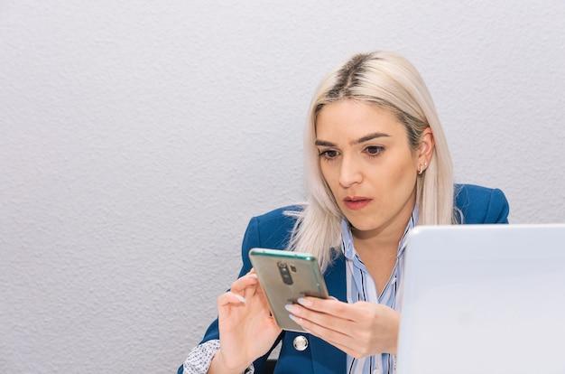 Junge blonde frau mit platinhaar gekleidet in einem blauen blazer teleworking von zu hause mit telefon und laptop. telearbeitskonzept.