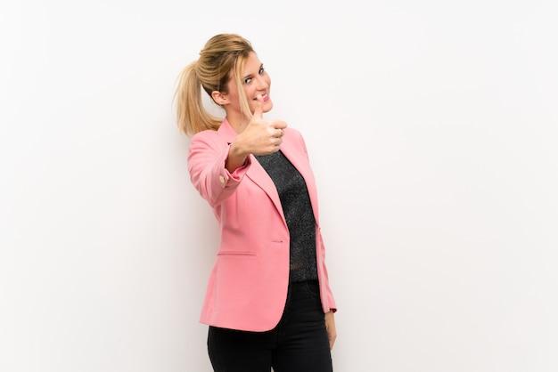 Junge blonde frau mit rosa anzug mit daumen nach oben, weil etwas gutes passiert ist
