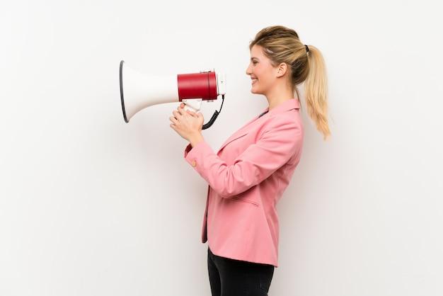 Junge blonde frau mit rosafarbener klage schreiend durch ein megaphon