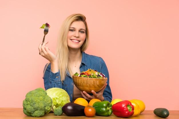 Junge blonde frau mit salat