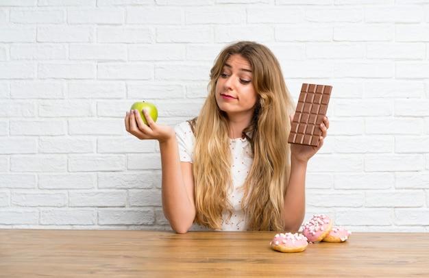 Junge blonde frau mit schokolade und einem apfel, der zweifel hat