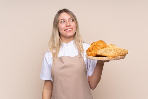 Junge blonde frau mit schürze. weiblicher bäcker, der einen tisch mit mehreren broten hält, die beim lächeln nach oben schauen