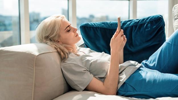 Junge blonde frau mit smartphone auf dem sofa liegend