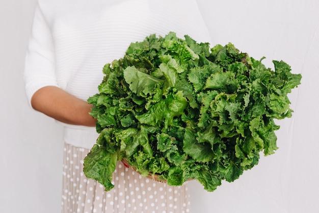 Junge blonde frau mit viel grünem salat