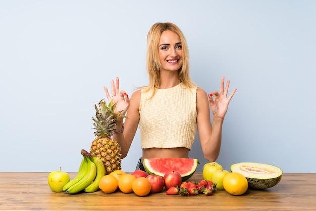 Junge blonde frau mit vielen früchten, die ein okayzeichen mit den fingern zeigen