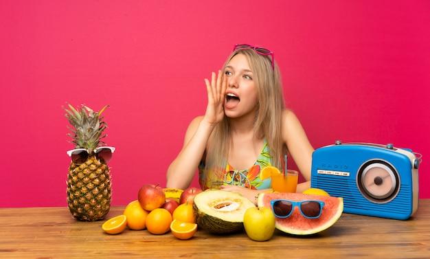 Junge blonde frau mit vielen früchten, die mit dem breiten mund schreien, öffnen sich
