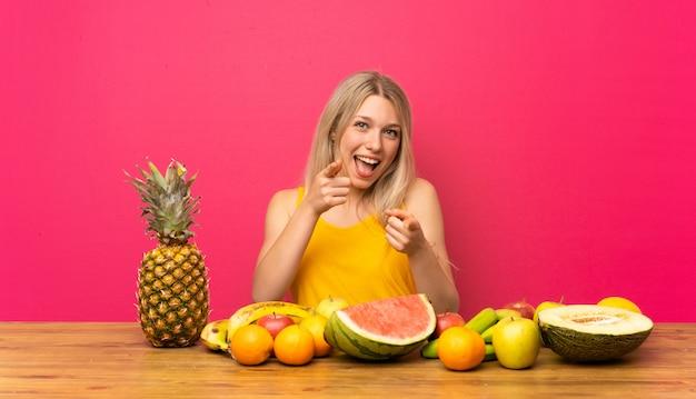 Junge blonde frau mit vielen früchten zeigt auf sie