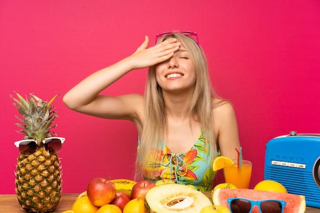 Junge blonde frau mit vielen früchten