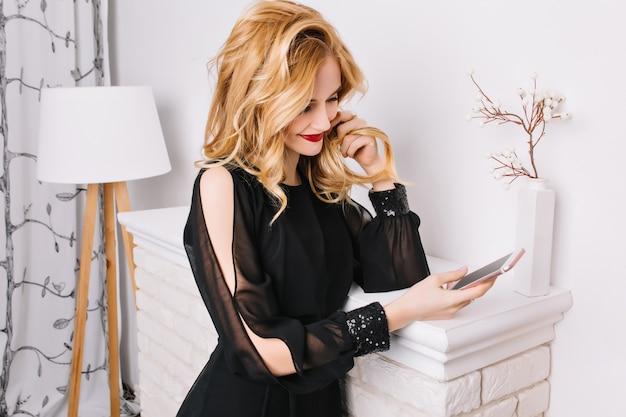 Junge blonde frau mit welligem haar, das ihr telefon betrachtet, das gegen gefälschten kamin im modernen raum mit weißem innenraum steht. trage ein stilvolles schwarzes kleid.