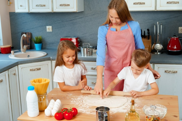 Junge blonde frau, mutter und ihre kinder, die spaß beim kochen des teigs haben