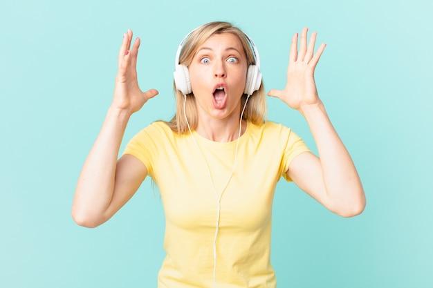 Junge blonde frau schreit mit den händen in die luft und hört musik.