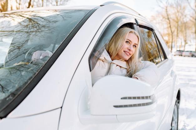 Junge blonde frau sitzen in ihrem neuen weißen auto und lächeln glücklich.