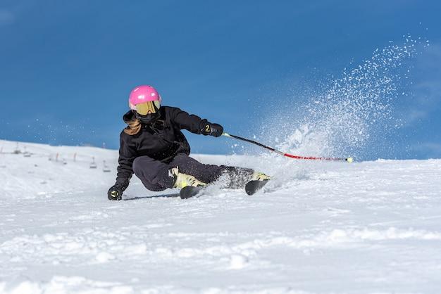 Junge blonde frau skifahren an einem sonnigen tag