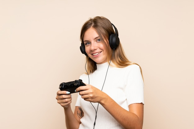 Junge blonde frau über der getrennten wand, die an den videospielen spielt