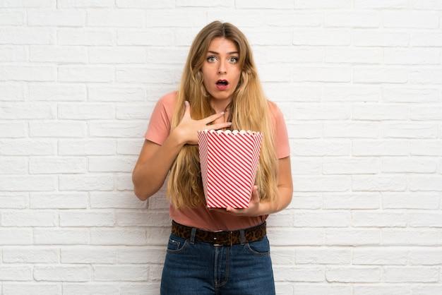 Junge blonde frau über der weißen backsteinmauer, die eine schüssel popcorn hält