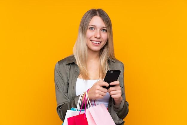 Junge blonde frau über gelb, die einkaufstaschen hält und eine nachricht schreibt