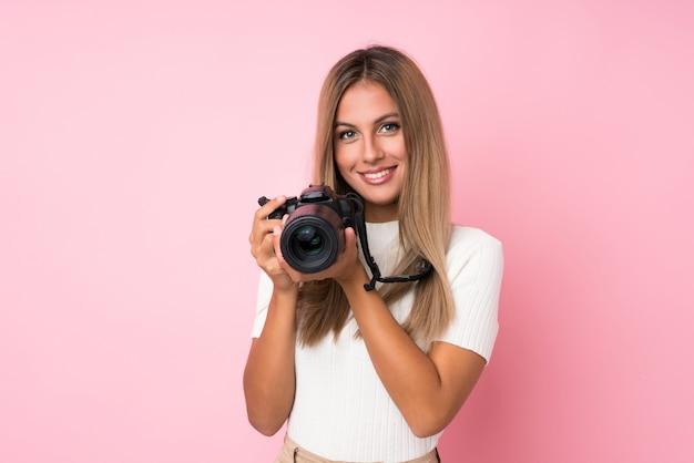 Junge blonde frau über getrenntem rosa mit einer berufskamera