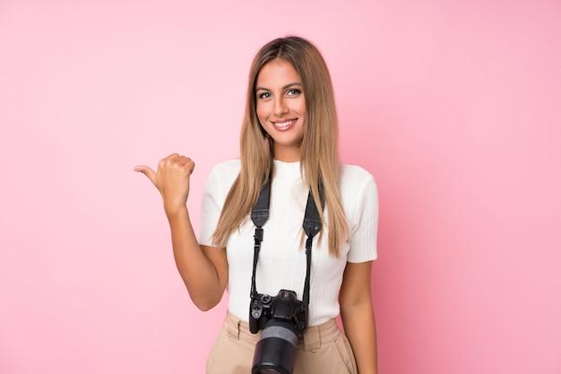Junge blonde frau über getrennter rosafarbener wand mit einer berufskamera und zeigen auf die seite