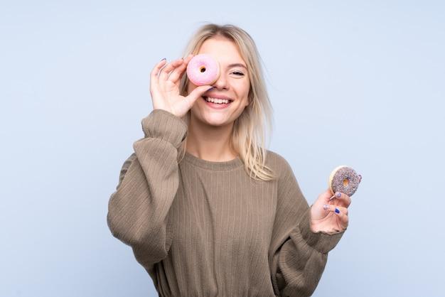 Junge blonde frau über isolierte blaue wand, die einen donut und glücklich hält