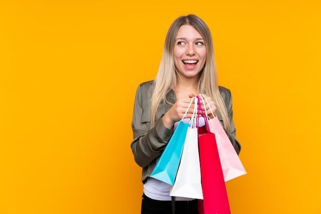 Junge blonde frau über isolierte gelbe wand, die einkaufstaschen hält und überrascht