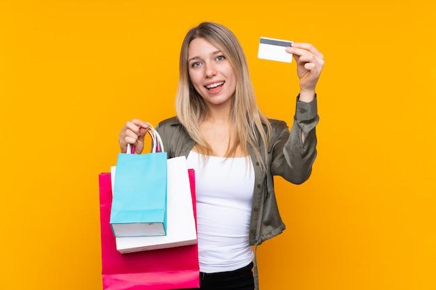 Junge blonde frau über isolierte gelbe wand, die einkaufstaschen und eine kreditkarte hält