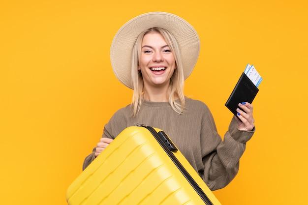 Junge blonde frau über isolierte gelbe wand im urlaub mit koffer und pass
